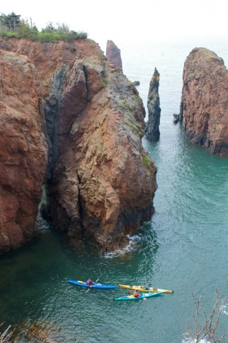 Kayakers explore the 'Three Sisters' rock formations that rise from the waters off the Bay of Fundy at Eatonville in Cape Chignecto Provincial Park - Credit Photo Nova Scotia Tourism